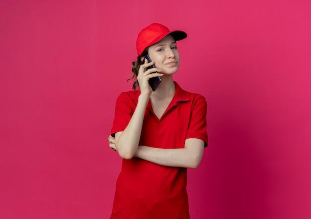 Unzufriedenes junges hübsches liefermädchen in der roten uniform und in der kappe, die mit geschlossener haltung steht, die am telefon spricht und kamera betrachtet, die auf purpurrotem hintergrund mit kopienraum lokalisiert wird