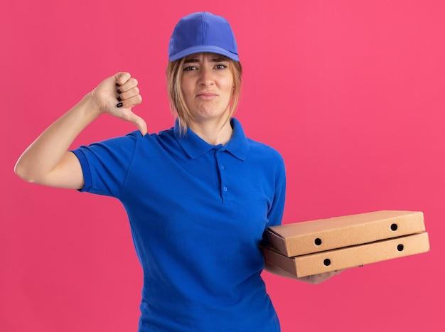 Unzufriedenes junges hübsches liefermädchen in uniform hält pizzaschachteln und daumen auf rosa