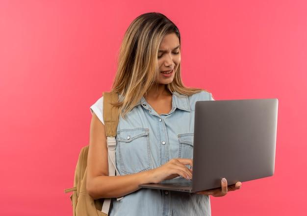 Unzufriedenes junges hübsches studentenmädchen, das rückentasche verwendet und laptop lokalisiert auf rosa hintergrund mit kopienraum trägt