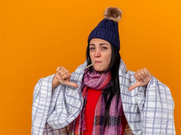 Unzufriedenes junges kaukasisches krankes mädchen, das wintermütze und schal wickelt, die im plaid halten, das thermometer im mund hält und kamera betrachtet, die daumen unten lokalisiert auf orangefarbenem hintergrund zeigt