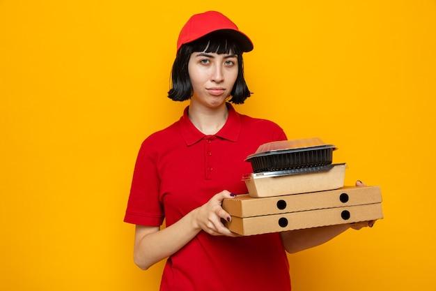 Unzufriedenes junges kaukasisches liefermädchen, das lebensmittelbehälter mit verpackung auf pizzakartons hält