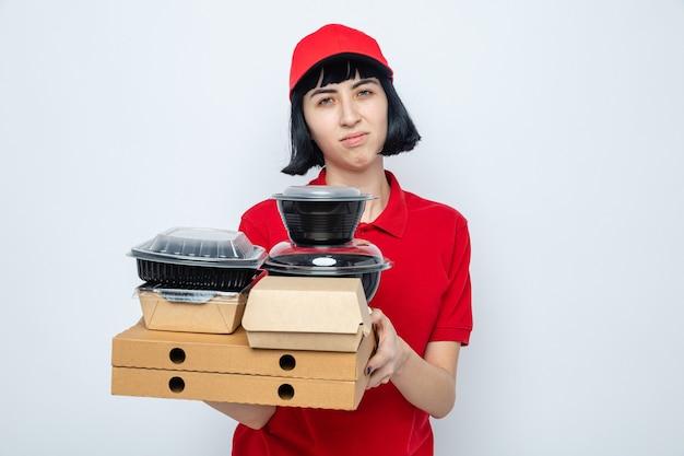 Unzufriedenes junges kaukasisches liefermädchen, das lebensmittelbehälter und verpackungen auf pizzakartons hält
