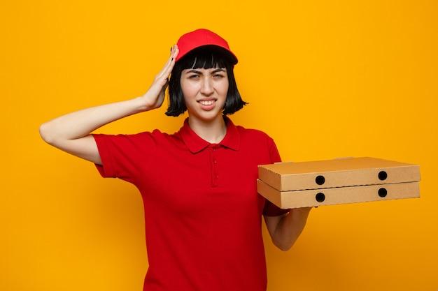 Unzufriedenes junges kaukasisches liefermädchen, das pizzakartons hält und die hand auf den kopf legt