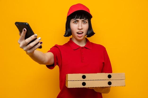 Unzufriedenes junges kaukasisches liefermädchen, das pizzakartons und telefon hält