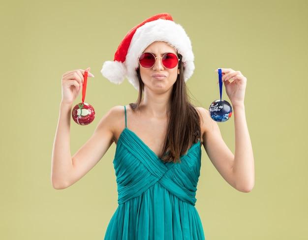 Unzufriedenes junges kaukasisches mädchen in sonnenbrille mit weihnachtsmütze, die glaskugelverzierungen hält