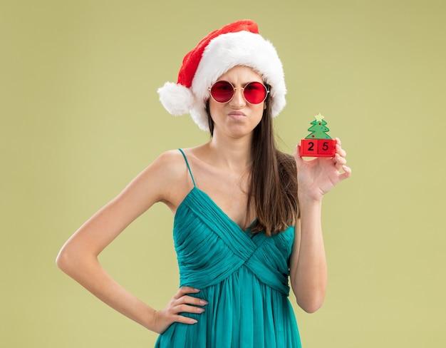 Unzufriedenes junges kaukasisches mädchen in sonnenbrille mit weihnachtsmütze, die weihnachtsbaumverzierung hält
