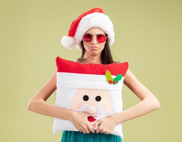 Unzufriedenes junges kaukasisches mädchen in sonnenbrille mit weihnachtsmütze, die weihnachtsmannkissen hält