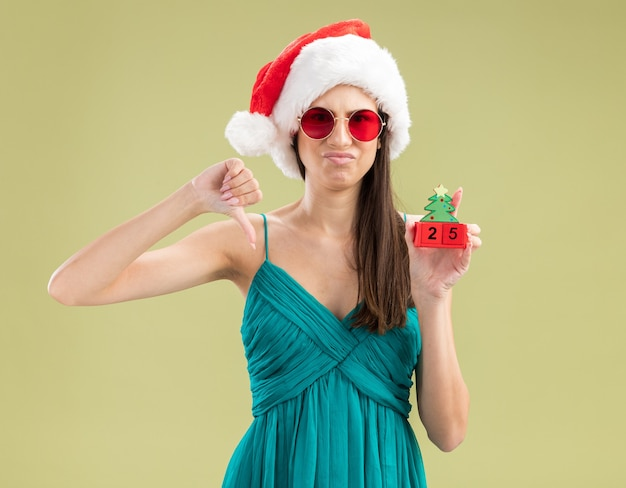 Unzufriedenes junges kaukasisches mädchen in sonnenbrille mit weihnachtsmütze hält weihnachtsbaumverzierung und daumen nach unten
