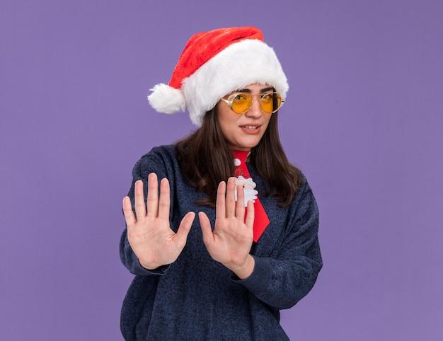Unzufriedenes junges kaukasisches mädchen in sonnenbrille mit weihnachtsmütze und weihnachtsmann-krawatte gestikuliert stoppschild mit händen isoliert auf lila wand mit kopierraum