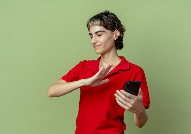 Unzufriedenes junges kaukasisches mädchen mit pixie-haarschnitt, der handy hält und nein mit geschlossenen augen gestikuliert auf olivgrünem hintergrund mit kopienraum
