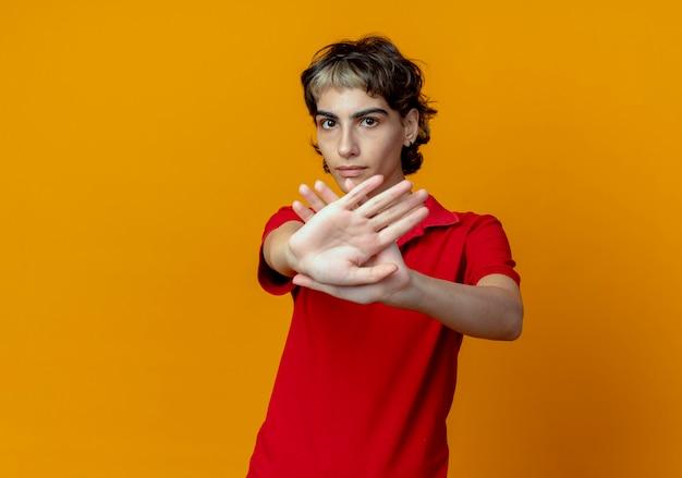 Unzufriedenes junges kaukasisches mädchen mit pixie-haarschnitt gestikuliert nein an der kamera lokalisiert auf orangefarbenem hintergrund mit kopienraum