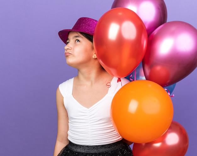 Unzufriedenes junges kaukasisches mädchen mit violettem partyhut, der heliumballons hält und lokalisiert auf lila wand mit kopienraum sucht