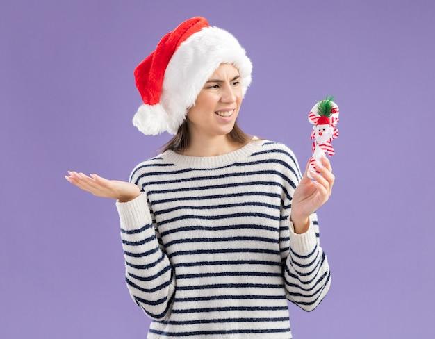 Unzufriedenes junges kaukasisches mädchen mit weihnachtsmütze, die zuckerstange hält und betrachtet