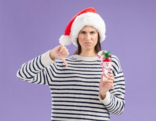 Unzufriedenes junges kaukasisches mädchen mit weihnachtsmütze hält zuckerstange und daumen nach unten