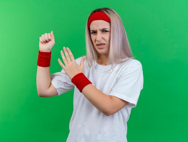 Unzufriedenes junges kaukasisches sportliches mädchen mit hosenträgern, das stirnband und armbänder trägt, hält die faust und hält die hand offen