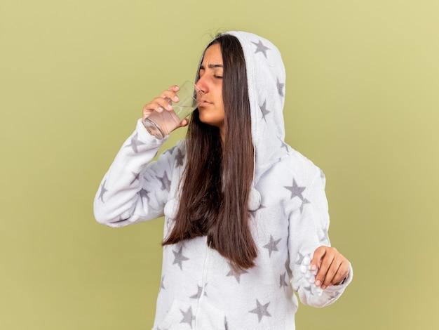Unzufriedenes junges krankes mädchen, das haube aufsetzt, trinkt wasser vom glas lokalisiert auf olivgrünem hintergrund