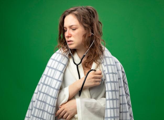 Unzufriedenes junges krankes mädchen, das seite betrachtet und weißes gewand trägt, das in plaid eingewickelt ist und ihren eigenen herzschlag mit stethoskop hört, das auf grün isoliert wird