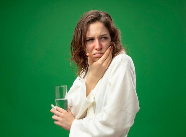 Unzufriedenes junges krankes mädchen, das seitliches tragen des weißen gewandes hält glas des wassers, das hand auf wange lokalisiert auf grün hält