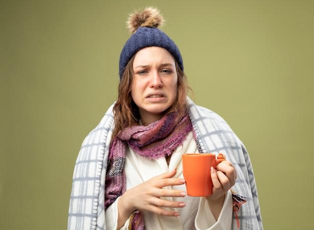 Unzufriedenes junges krankes mädchen, das weiße robe und wintermütze mit schal wickelt, der in plaid eingewickelt hält tasse des tees lokalisiert auf olivgrün