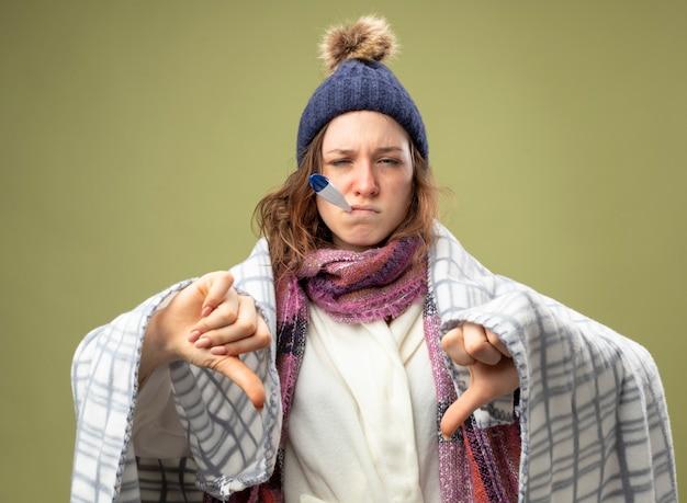Unzufriedenes junges krankes mädchen, das weiße robe und wintermütze mit schal wickelt, der in plaid gewickeltes thermometer in den mund wickelt und daumen nach unten isoliert auf olivgrün zeigt
