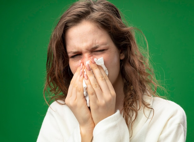 Unzufriedenes junges krankes mädchen, das weißes gewand trägt, das nase mit serviette abwischt, lokalisiert auf grün