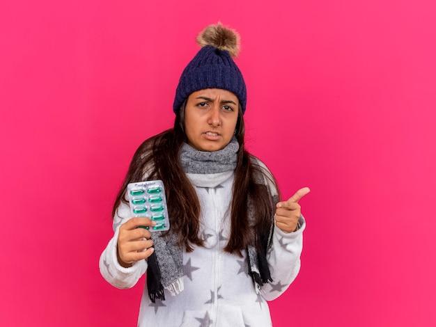 Unzufriedenes junges krankes mädchen, das wintermütze mit schal hält, der pillen hält, die sie geste lokalisiert auf rosa zeigen