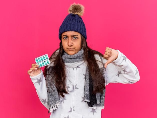 Unzufriedenes junges krankes mädchen, das wintermütze mit schal hält, der pillen hält und daumen unten lokalisiert auf rosa hintergrund zeigt