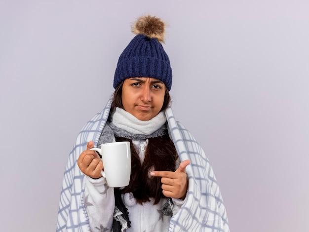 Unzufriedenes junges krankes mädchen, das wintermütze mit schal trägt, der im karierten halten eingewickelt wird und auf tasse tasse zeigt
