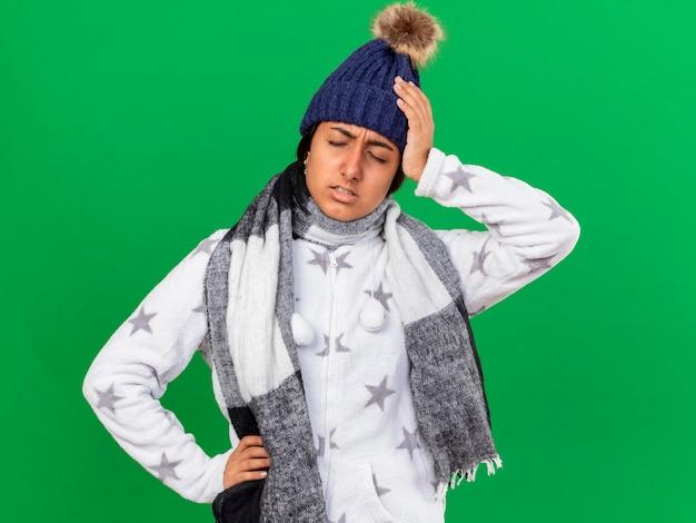 Unzufriedenes junges krankes mädchen, das wintermütze mit schal trägt, die hände auf schmerzenden kopf und hüfte lokalisiert auf grün setzen