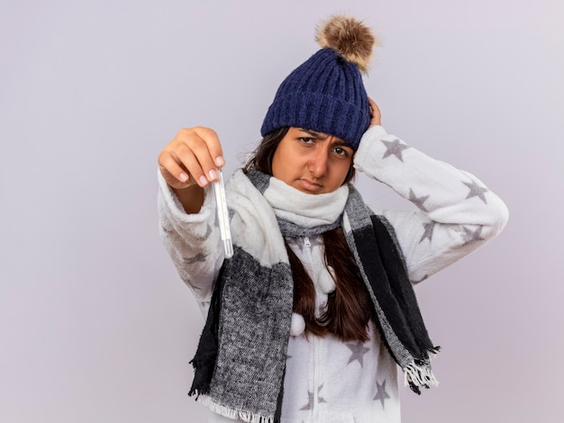 Unzufriedenes junges krankes mädchen, das wintermütze mit schal trägt hand auf kopf setzt und thermometer an kamera lokalisiert auf weißem hintergrund mit kopienraum hält Kostenlose Fotos