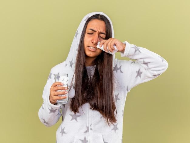 Unzufriedenes junges krankes mädchen mit geschlossenen augen, die auf haube setzen glas des wassers mit pillen abwischen nase mit serviette lokalisiert auf olivgrünem hintergrund