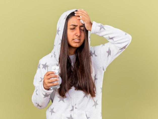 Unzufriedenes junges krankes mädchen mit geschlossenen augen, die haube halten glas des wassers mit pillen und hand auf stirn lokalisiert auf olivgrünem hintergrund setzen