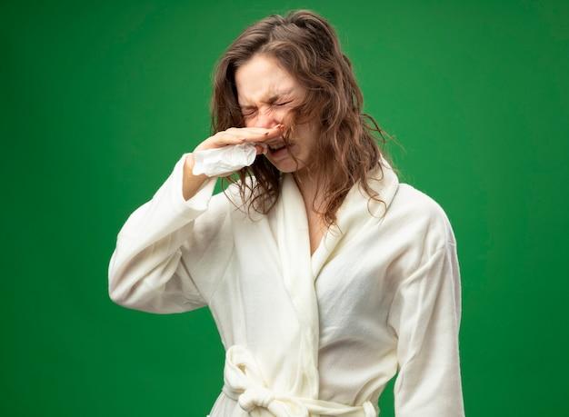Unzufriedenes junges krankes mädchen mit geschlossenen augen, die weiße robe tragen, die nase mit serviette abwischt, die auf grün isoliert wird