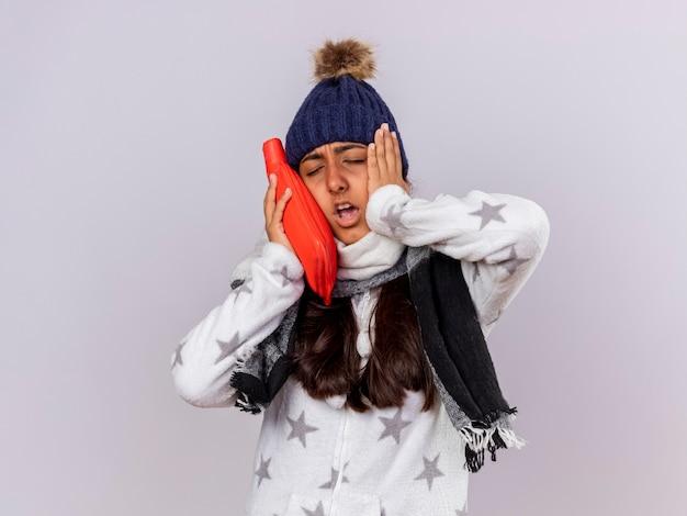 Unzufriedenes junges krankes mädchen mit geschlossenen augen, die wintermütze mit schal tragen heißes sackwasser auf wange setzen