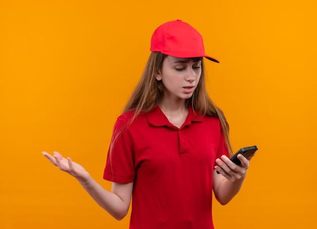 Unzufriedenes junges liefermädchen in der roten uniform, die handy hält, das es betrachtet, das leere hand auf isolierter orange wand zeigt