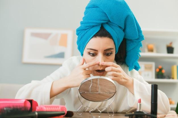 Unzufriedenes junges mädchen, das den spiegel betrachtet, drückt pickel eingewickeltes haar in ein handtuch, das am tisch mit make-up-tools im wohnzimmer sitzt