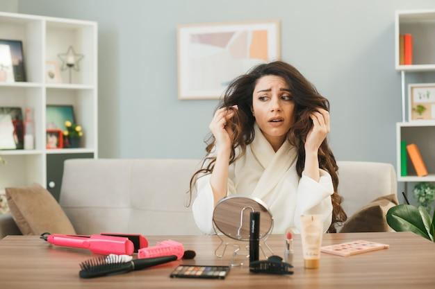 Unzufriedenes junges mädchen, das mit make-up-tools im wohnzimmer am tisch sitzt, packte haare