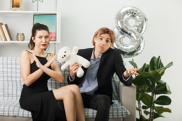 Unzufriedenes junges paar am glücklichen frauentag mit teddybärmädchen, das die geste zeigt, nicht auf dem sofa im wohnzimmer zu sitzen