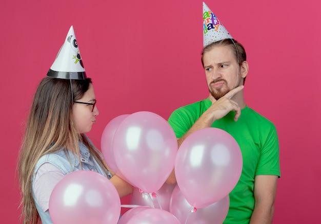 Unzufriedenes junges paar, das partyhut trägt, schaut einander stehend mit heliumballons an, die auf rosa wand isoliert werden