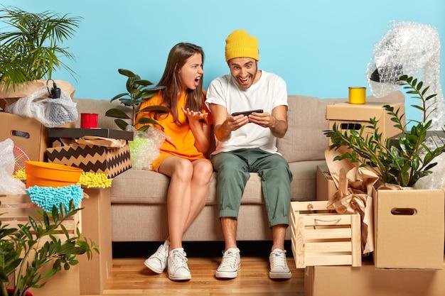Unzufriedenes junges paar sitzt auf der couch, umgeben von kisten