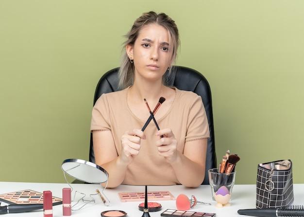 Unzufriedenes junges schönes mädchen, das am schreibtisch mit make-up-tools sitzt und make-up-pinsel auf olivgrünem hintergrund hält und kreuzt