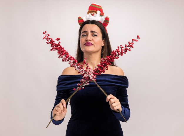 Unzufriedenes junges schönes mädchen, das blaues kleid und weihnachtshaarbügel hält und ebereschenzweig lokalisiert auf weißem hintergrund trägt