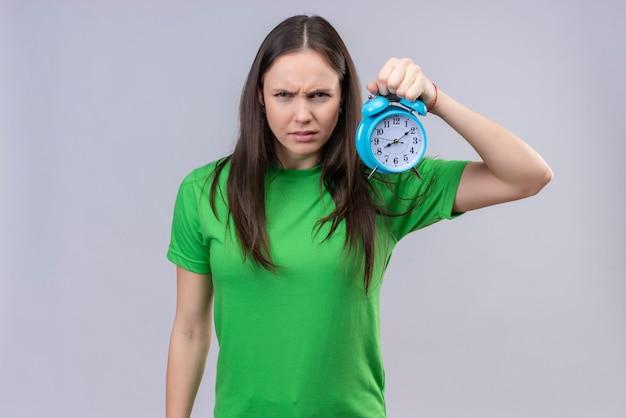 Unzufriedenes junges schönes mädchen, das grünes t-shirt hält, das wecker mit stirnrunzelndem gesicht hält, das über isoliertem weißem raum steht