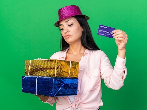 Unzufriedenes junges schönes mädchen mit partyhut, das geschenkboxen mit kreditkarte hält