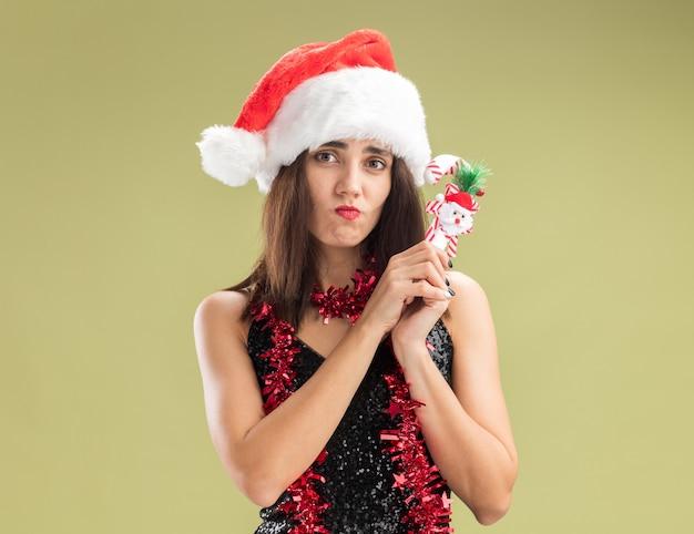 Unzufriedenes junges schönes mädchen mit weihnachtsmütze mit girlande am hals, das weihnachtsspielzeug isoliert auf olivgrünem hintergrund hält