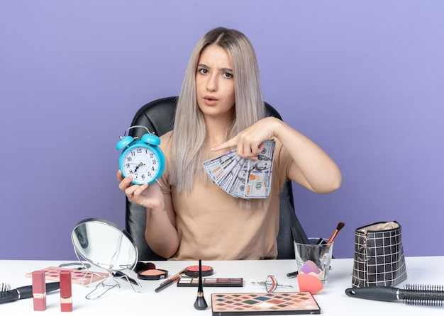 Unzufriedenes junges schönes mädchen sitzt am tisch mit make-up-tools, die bargeld und punkte am wecker in der hand halten, isoliert auf blauem hintergrund