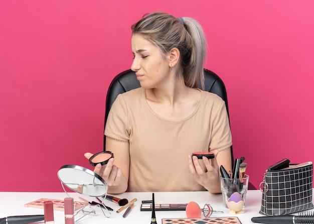 Unzufriedenes junges schönes mädchen sitzt am tisch mit make-up-tools, die puderröte einzeln auf rosa hintergrund halten