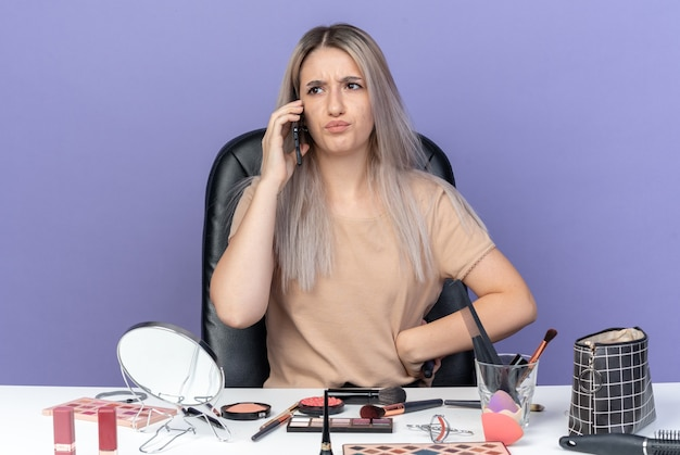 Unzufriedenes junges schönes mädchen sitzt am tisch mit make-up-tools spricht am telefon und hält einen kamm, der die hand auf die hüfte legt, isoliert auf blauem hintergrund