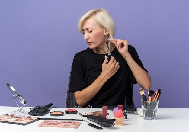 Unzufriedenes junges schönes mädchen sitzt am tisch mit make-up-werkzeugen, die haare mit einer schere auf blauem hintergrund schneiden