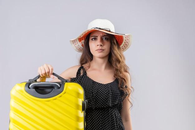 Unzufriedenes junges schönes reisendes mädchen im kleid im tupfen im sommerhut, der koffer mit wütendem stirnrunzelndem gesicht hält